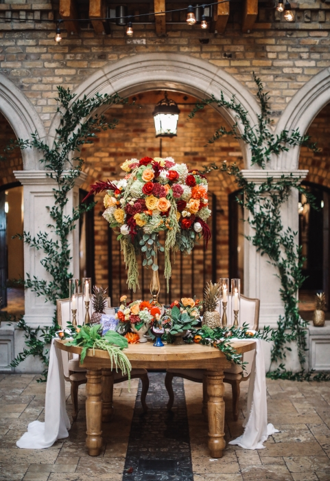 HIgh and low table design with ivy decor in background}