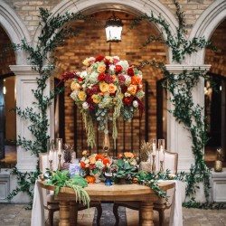 HIgh and low table design with ivy decor in background